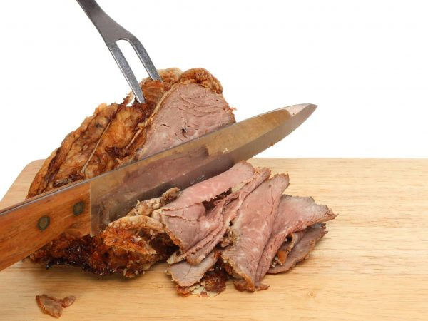 16642255 – carving roast beef, meat joint with a carving knife and fork on a wooden board