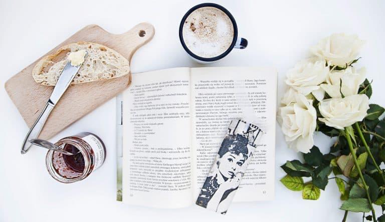 Buch mit Rosen, Tasse Kaffe und Brot mit Messer