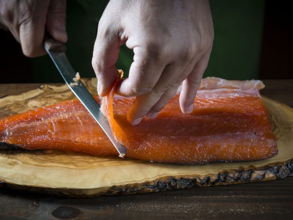 Slicing gravlax salmon with a knife on a cutting board